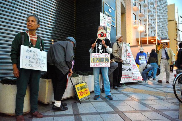 「キンカン行動」で原発再稼働反対を訴える人たち=下京区
