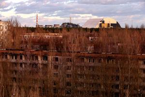 4月26日で事故から30年を迎えるチェルノブイリ原発4号炉(中央)。老朽化した「石棺」を覆う新シェルター(右)の建設が進む。原発から約3キロにあるプリピャチは原発職員の街だったが、全住民が避難。市街地の集合住宅(手前)は廃虚と化し、森にのみ込まれてゆく=2日、ウクライナ、杉本康弘撮影