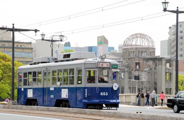 原爆ドームをバックに走る被爆電車=広島市中区