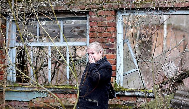 故郷のボロービチ村から避難したスベトラーナさんは、かつて住んでいた家の2階が崩れ落ち、居間には木が生い茂った様子を目にして涙した=3月22日、ウクライナ