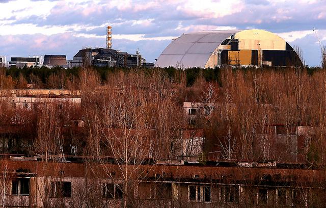 事故から30年を迎えるチェルノブイリ原発4号炉(中央)。老朽化した「石棺」を覆う新シェルター(右)の建設が進む。原発から約3キロにあるプリピャチは原発職員の街だったが、全住民が避難。市街地の集合住宅(手前)は廃虚と化し、森にのみ込まれてゆく=2日、ウクライナ、杉本康弘撮影