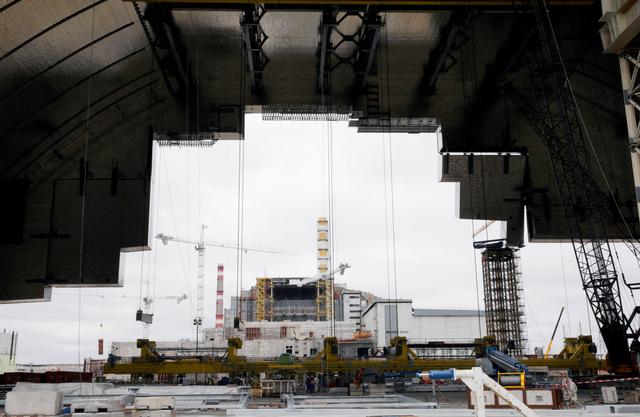 巨大な新シェルターから見た4号炉(奥)=3月23日、ウクライナ、杉本康弘撮影