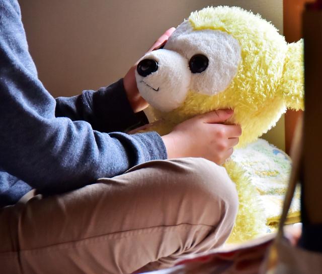 女子生徒が気に入っていたというクマのぬいぐるみを手にする幼なじみ=金沢市