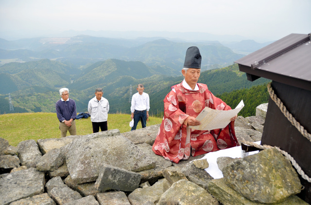 山頂で例祭を行う田村さん(右)ら=美祢市