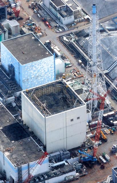 福島第一原発の1号機(中央)と排気筒(右)=3月12日朝日新聞社ヘリから、堀英治撮影