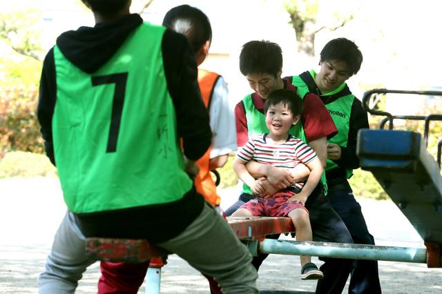 避難所の小学校でボランティアたちに遊んでもらい、笑顔を見せる子ども(中央)=22日、熊本市、吉本美奈子撮影