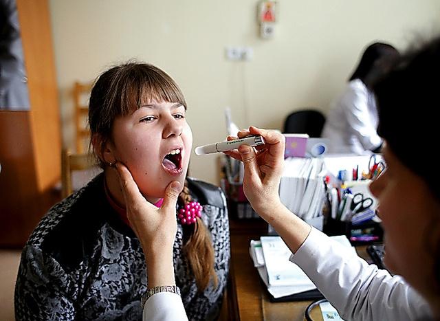 微熱が続き母親のスベトラーナさんと国立病院を訪れたアナスタシアさん=3月31日、ベラルーシ・ゴメリ州