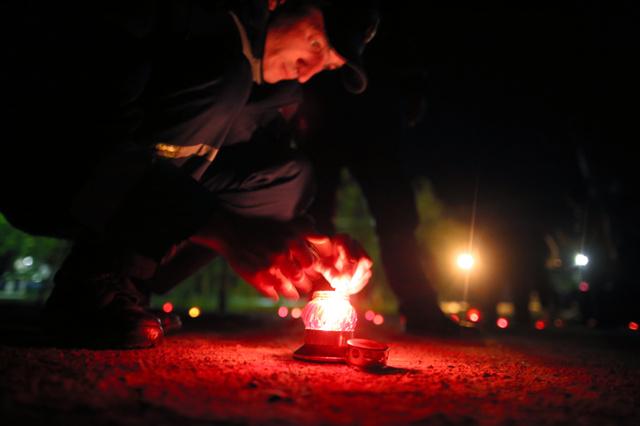 チェルノブイリ市中心部の広場で25日夜、住民らが追悼の式典を開いた。事故で住めなくなった村々や多くの犠牲者に思いをはせ、消防士らが鎮魂のロウソク約100本に火をともした。地元出身の画家アレクサンドルさん(55)は「失われた人の命を忘れない」と語った=矢木隆晴撮影