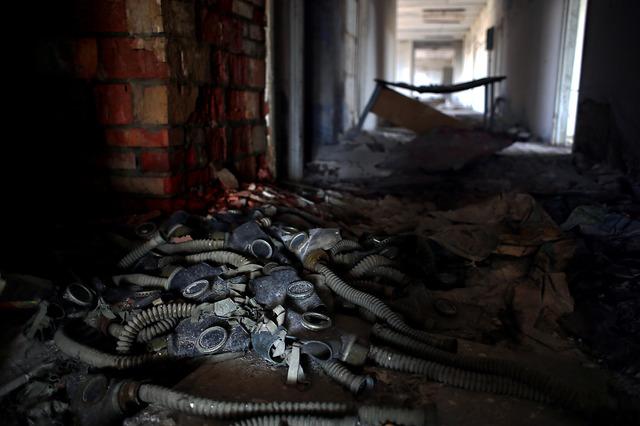 廃虚となった2階建て校舎。窓ガラスは割れ、机や椅子も残されたままだ。階段に散らばるガラスを踏みながら2階に上がると、廊下にはガスマスクが散乱していた