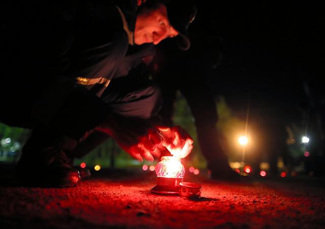 <失われた村へ 人へ> チェルノブイリ市中心部の広場で25日夜、住民らが追悼の式典を開いた。事故で住めなくなった村々や多くの犠牲者に思いをはせ、消防士らが鎮魂のロウソク約100本に火をともした。地元出身の画家アレクサンドルさん(55)は「失われた人の命を忘れない」と語った=矢木隆晴撮影
