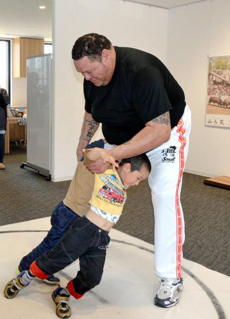 保育園児と相撲を取る曙太郎さん(右)=長岡市の山古志復興交流館おらたる