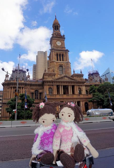 シドニーの観光名所・タウンホール前で記念写真に納まった姉妹の人形。右が姉の愛梨ちゃん