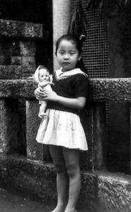 小学低学年。髪の毛はロングだった。当時住んでいた東京都中野区の若葉荘前で。「ジョージ」と名前をつけた米国のセルロイド人形を抱いた思い出の1枚=本人提供