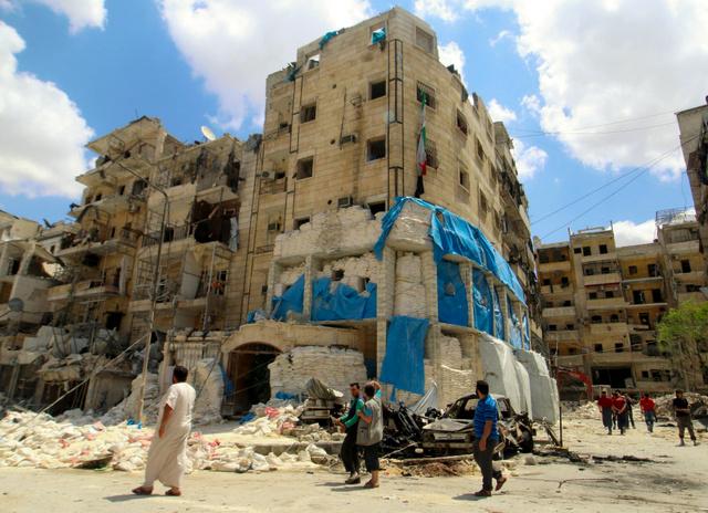 シリア・アレッポで28日、空爆された病院の被害を調べる人たち=ロイター