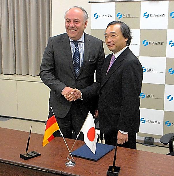 署名式で握手するドイツのマハニック・経済エネルギー省次官(左)と上田隆之・経済産業審議官=東京・霞が関