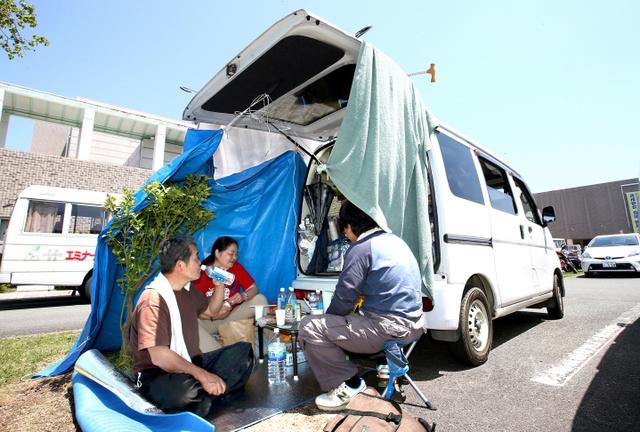 地震発生から、駐車場で車中泊の避難生活を続ける横田光秋さん(58・左端)夫妻。日差しが強くなり、シートやタオルを広げてしのいでいた。「熱中症には気をつけています。梅雨や蚊の季節になったら屋内での避難生活も考えないと。それまでに仮設が出来れば」。1日に始まった罹災(りさい)証明書の受け付けには朝9時から並んだ=1日午後0時57分、熊本県益城町、遠藤啓生撮影