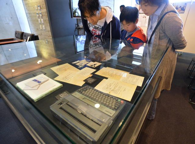 阪神支局3階の襲撃事件資料室で、展示されたワープロなどを見る人たち=3日、西宮市、水野義則撮影