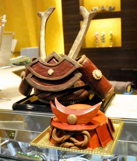 5日まで限定販売されている赤兜の形のケーキ(手前)。後ろに菓子細工の兜も飾られている=大阪市北区
