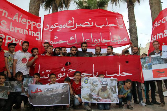 シリア北部イドリブで4日、アレッポ住民への連帯を示して座り込みをする人たち=ロイター