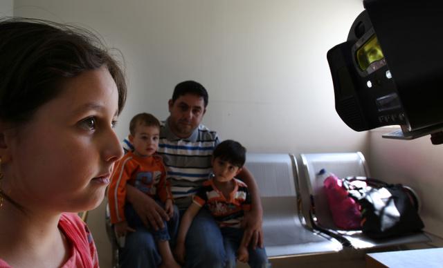 UNHCRの施設で、虹彩(こうさい)を読み取る装置を見つめる8歳のシリア難民のテスニームさん(左)。1年ごとに再登録を求められるという=4月20日、ヨルダン北部イルビド、矢木隆晴撮影