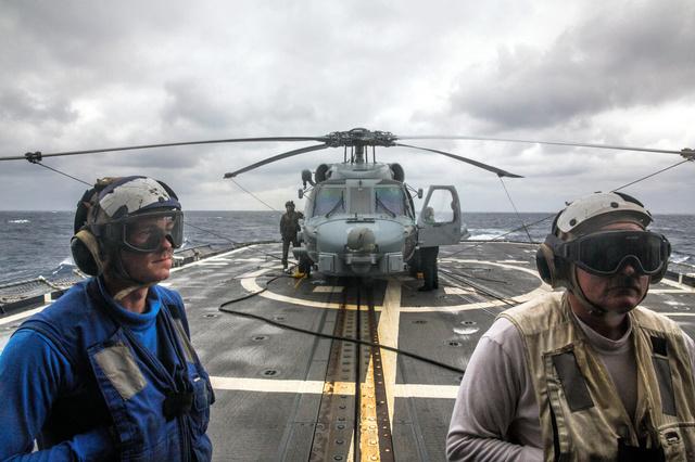 巡洋艦チャンセラーズビルの甲板上で、ヘリコプターの離陸準備をする乗組員たち=(C)2016 Bryan Denton/The New York Times