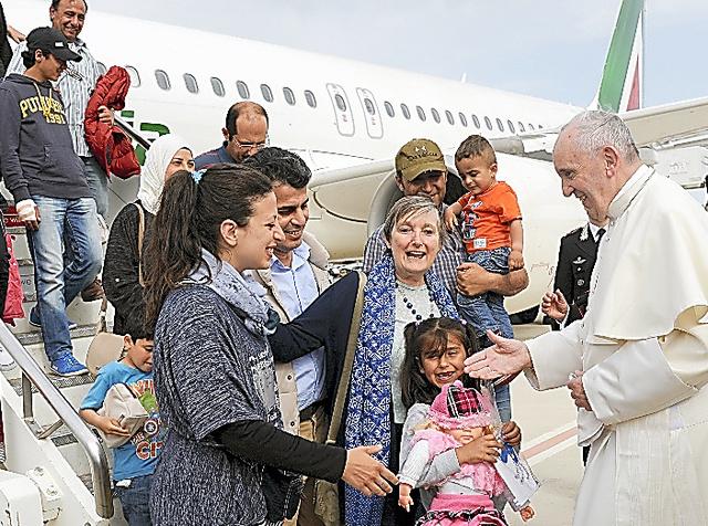 4月16日、ローマの空港でフランシスコ法王の歓迎を受けるシリア人難民ら=ロイター