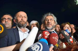 判決後に会見し、「私たちは圧力に屈しない。事実を伝え続ける」と語ったジュムフリエット紙編集長のジャン・ドゥンダル氏(中央右)と、アンカラ支局長のエルデム・ギュル氏(同左)=6日夕、イスタンブール、メスット・クチュクアルスラン撮影