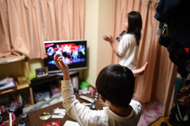 夕飯前、大好きなグループのDVDを見ながら踊る次男と長女=伊藤進之介撮影