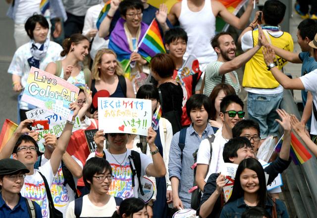 メッセージを掲げた参加者たちは沿道の人たちとハイタッチしながらパレードをした=8日午後、東京・渋谷、金居達朗撮影