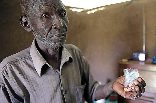 マラリアの治療薬を手にするオチョラさん。マラリアで4人の子どもを失った=キスム郊外、三浦英之撮影