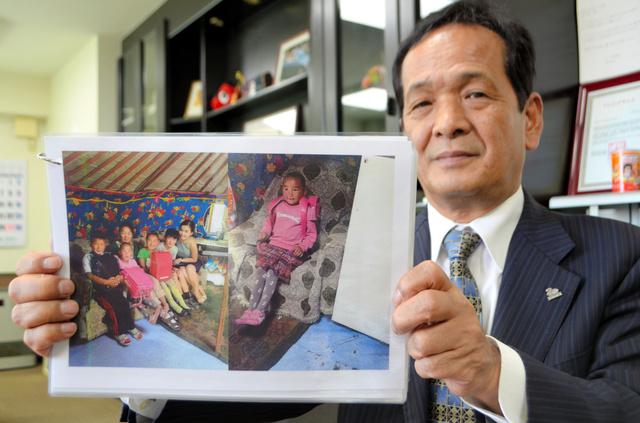 ランドセルを背負うモンゴルの小学生の写真を見せる弓田八平さん=会津若松市