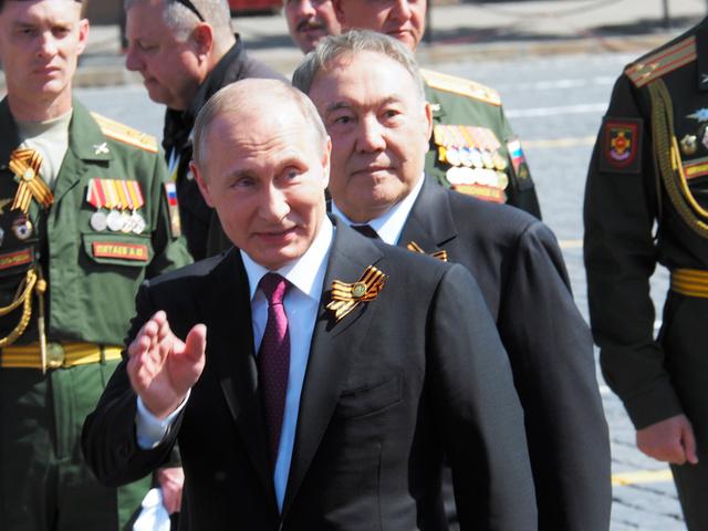 赤の広場の軍事パレード終了後、会場の退役軍人らに手を振るプーチン大統領。後ろはカザフスタンのナザルバエフ大統領=9日、モスクワ、駒木明義撮影