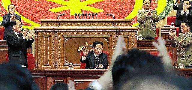 9日、朝鮮労働党大会で参加者の拍手に応える金正恩氏(中央)=AP
