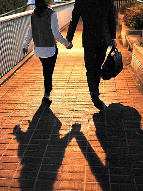 手をつないで帰る男性と妻=内田光撮影