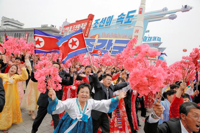 北朝鮮の平壌で10日、大規模なパレードのさなか、姿を見せた金正恩氏に両手をあげて応える人たち=ロイター