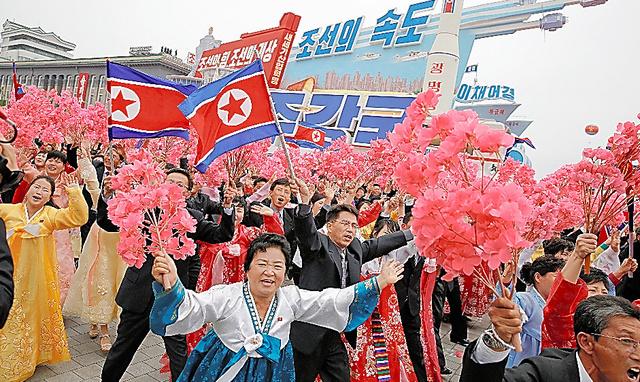 平壌で10日、大規模なパレードのさなか、姿を見せた金正恩氏に両手をあげて応える人たち=ロイター