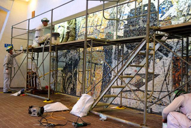村井正誠氏原画のモザイク壁画を壁からはがす作業員たち=新宮市新宮