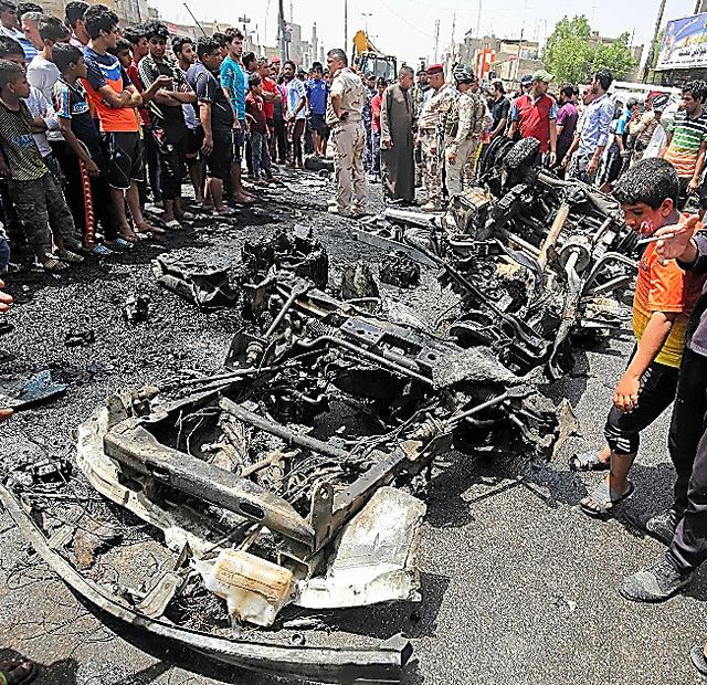 バグダッドの「サドルシティー」で11日、爆発の現場に集まった人たち=AFP時事