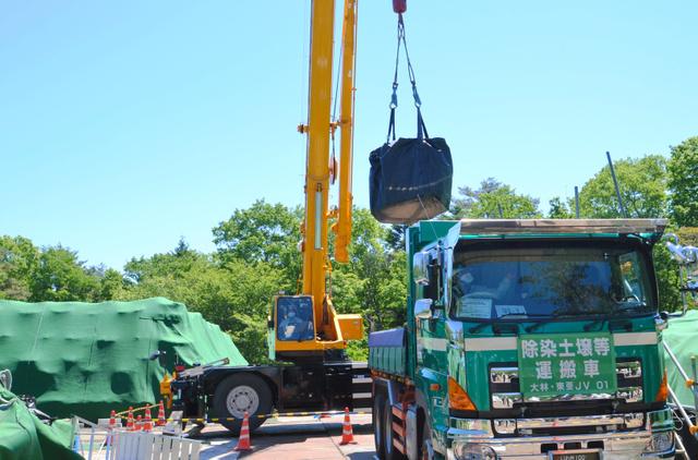 中間貯蔵施設の予定地へ運ぶため、汚染土の入った袋がダンプカーに積み込まれた=双葉町