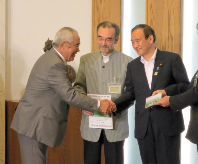 会議後、菅義偉官房長官と握手をする加藤忠・道アイヌ協会理事長(左)=首相官邸