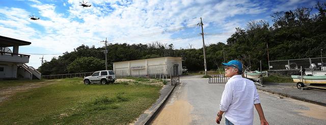 米軍の新しい飛行場建設が計画される沖縄・辺野古の周辺を歩く。重低音を響かせて、頭上にヘリコプターが飛来した=沖縄県名護市