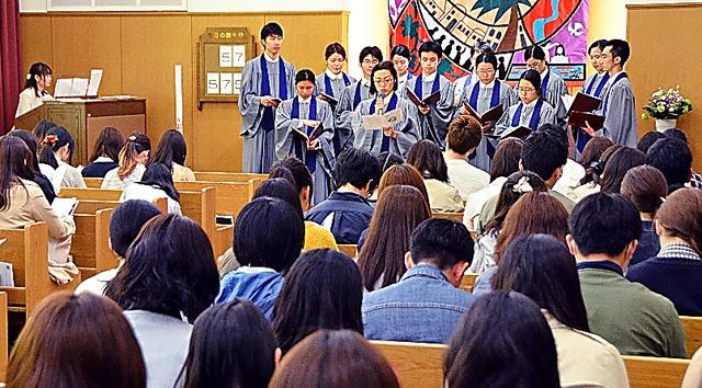 関西学院大文学部のチャペルアワーで、聖歌隊の指導で賛美歌を練習する学生ら=兵庫県西宮市