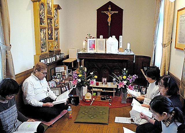 きぼうのいえの礼拝堂で開かれた「お別れの会」。山本雅基さん(左から2人目)らが祈りを捧げた=1月、東京都台東区