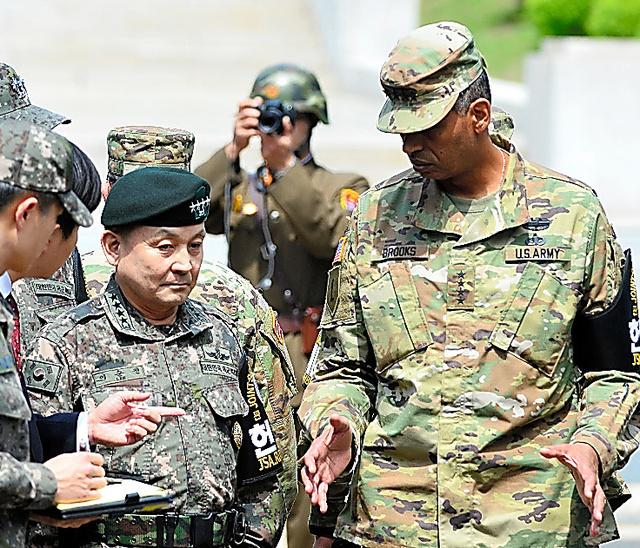 12日、板門店を訪れた新任のブルックス在韓米軍司令官(右)を撮影する北朝鮮軍兵士(後方)=東亜日報提供