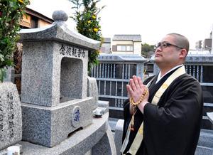 永代供養墓の前で手を合わせる純空壮宏さん。僧侶派遣会社を通じて知った遺族らが遺骨を納めている=大阪市天王寺区