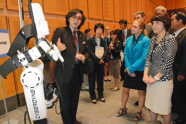 「ロボットスーツHAL」の説明に耳を傾ける米国政府関係者と島尻科技相(右端)=つくば市の国際会議場