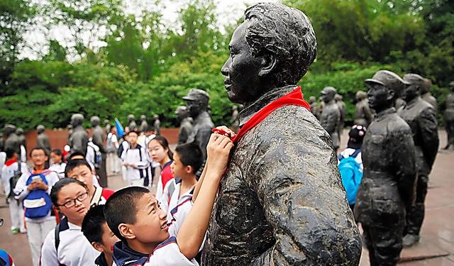 中国・四川省で13日、毛沢東の像に赤いスカーフをまく子ども=ロイター
