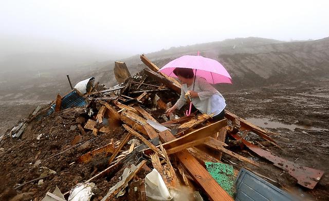 <今でも、会いたい> 本震で5人が犠牲となった南阿蘇村の高野台地区。亡くなった前田友光さん(当時65)の妻の和子さんは、がれきの中から友光さんの遺品を探した。「会いたかった。今でも、会いたい。ただ会いたいだけです」=16日午前11時59分、金子淳撮影