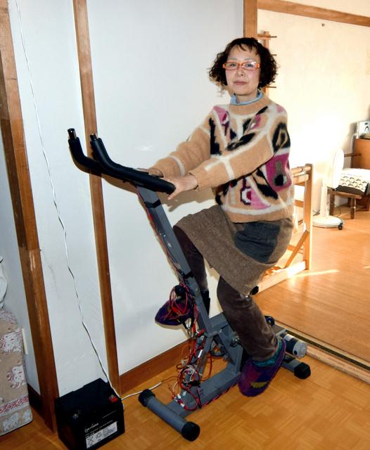 電気代ゼロ生活を続ける藤井智佳子さん。緊急時は自転車型トレーニングマシンを改造した「人力発電機」で電気をつくる=国立市