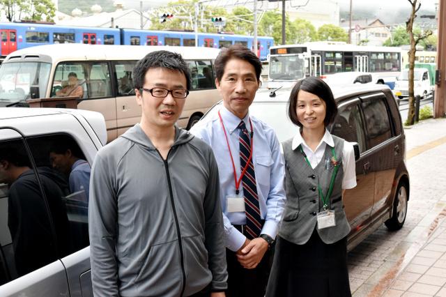 車を提供した「イワテック」代表取締役の岩元孝一郎さん(中央)と中里絵美さん(右)。左は「日本カーシェアリング協会」代表理事の吉沢武彦さん。後ろの2台が提供された車=長崎市宝町のイワテック本社前